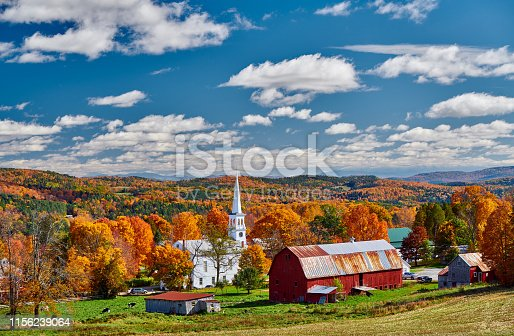 488912426istockphoto Church and farm with red barn at autumn 1156239064