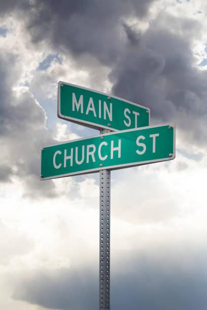 kirche und der main street - straßenschild stock-fotos und bilder