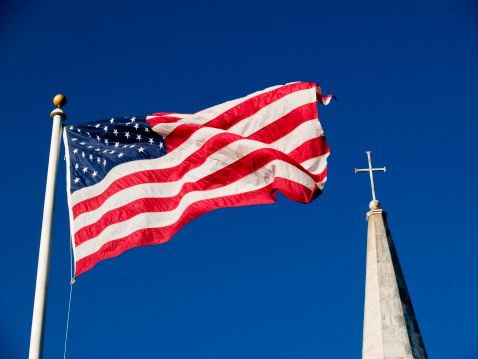 American flag and church steeple against very clear blue sky