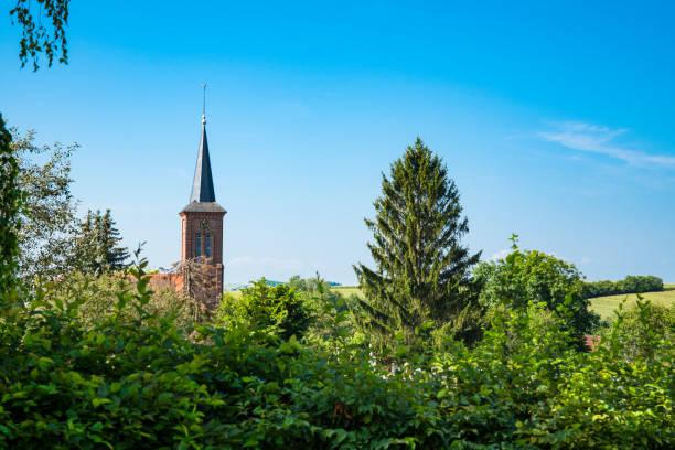 kyrkan och träden i hunspach, frankrike - hunspach bildbanksfoton och bilder
