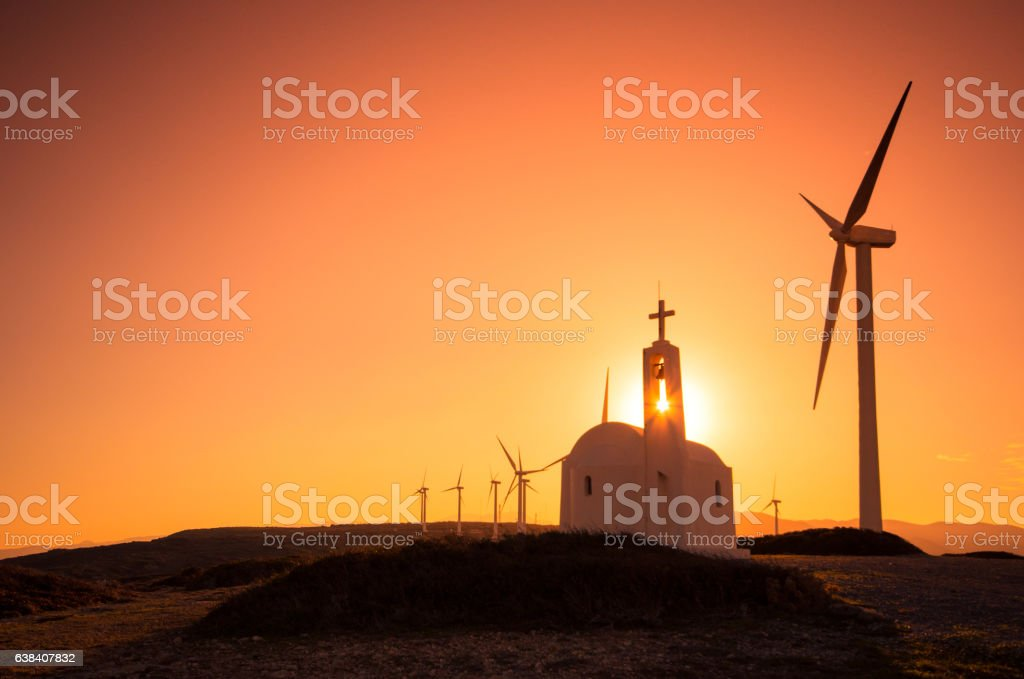 Church and wind turbines at sunset. stock photo