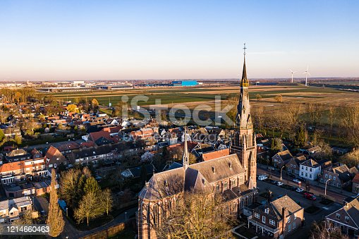 A church and windmills during sunrise on a sunny morning in the dutch town of Waalwijk, Noord Brabant, Netherlands