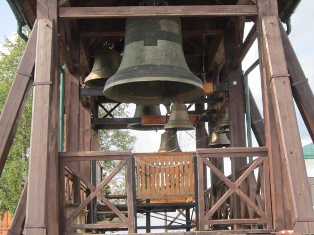 kerk bell - klokkentoren met luidende klokken stockfoto's en -beelden