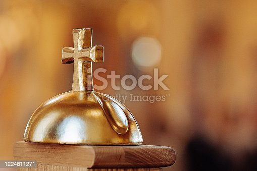 Church bell with a golden cross on a beautiful blurry background.