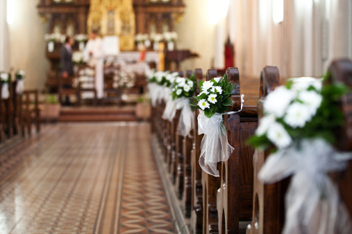 Church decorated with flower bouquets during the Wedding ceremony, selective focus.