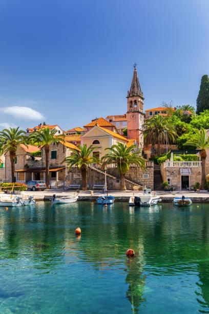 Kirchenbau und Palme gegen sonnigen blauen Himmel in Splitska Dorf auf der Insel Brac, Kroatien. – Foto