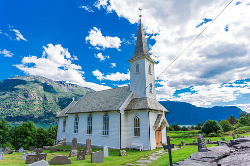 A brilliantly white church by a Fjord near mountains. This Norwegian religious building houses a cemetery for the local hamlet that stay in the quiet Sogndal County.