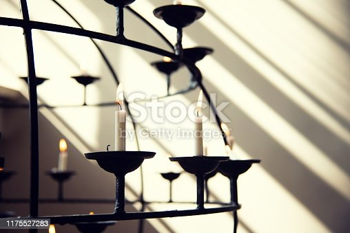 A church candle holder in front of a large, sunny window.