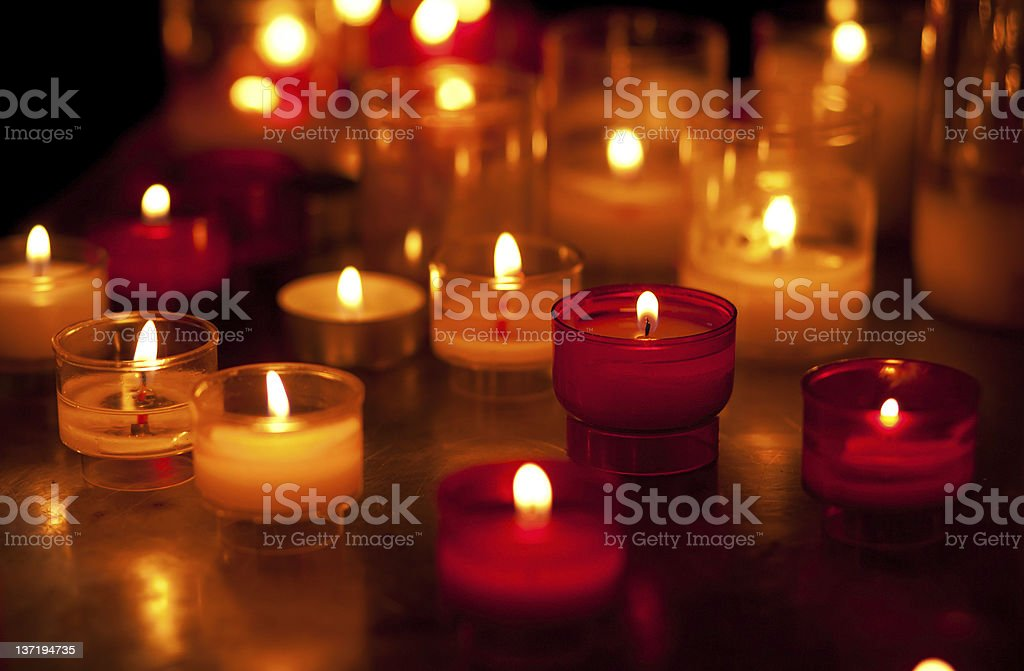 Church candles in red and yellow transparent chandeliers stock photo