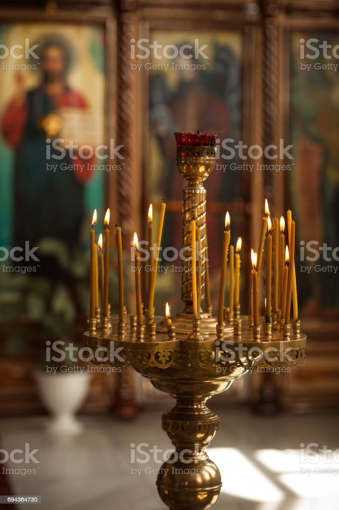 Church candles on the background of icons stock photo