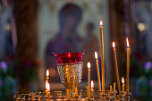 Church candles on the background of icons. Religion.