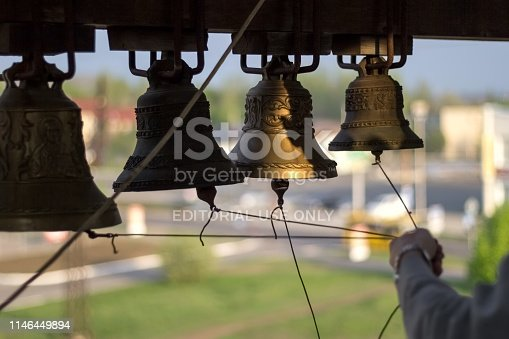 Church chimes and knot of ropes in hand of bell-ringer on belfry of Trinity Cathedral, during bells ringing on Easter celebrating. Ukraine, Donetsk, April 28, 2019 year.