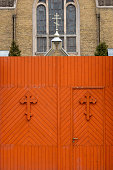 Church fence wooden gate in orange with crosses - image