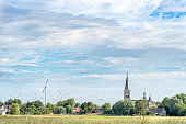 A church in a small town surrounded by wind mills under a blue and cloudy sky