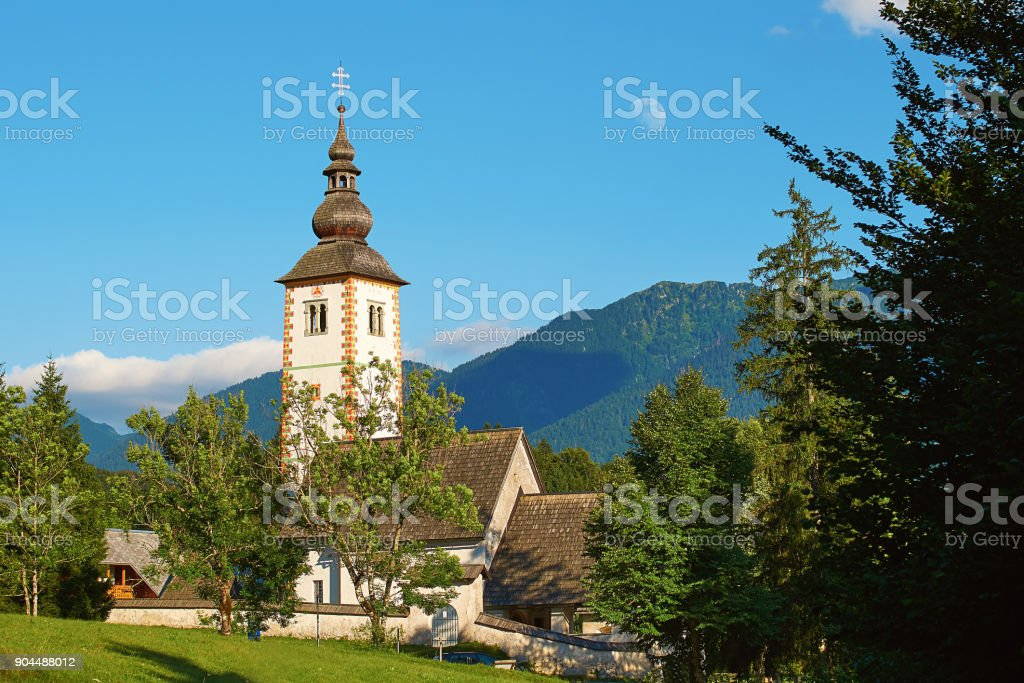 Church in Ribcev Laz, Slovenia located on the shore of lake Bohinj with a daytime moon over it stock photo