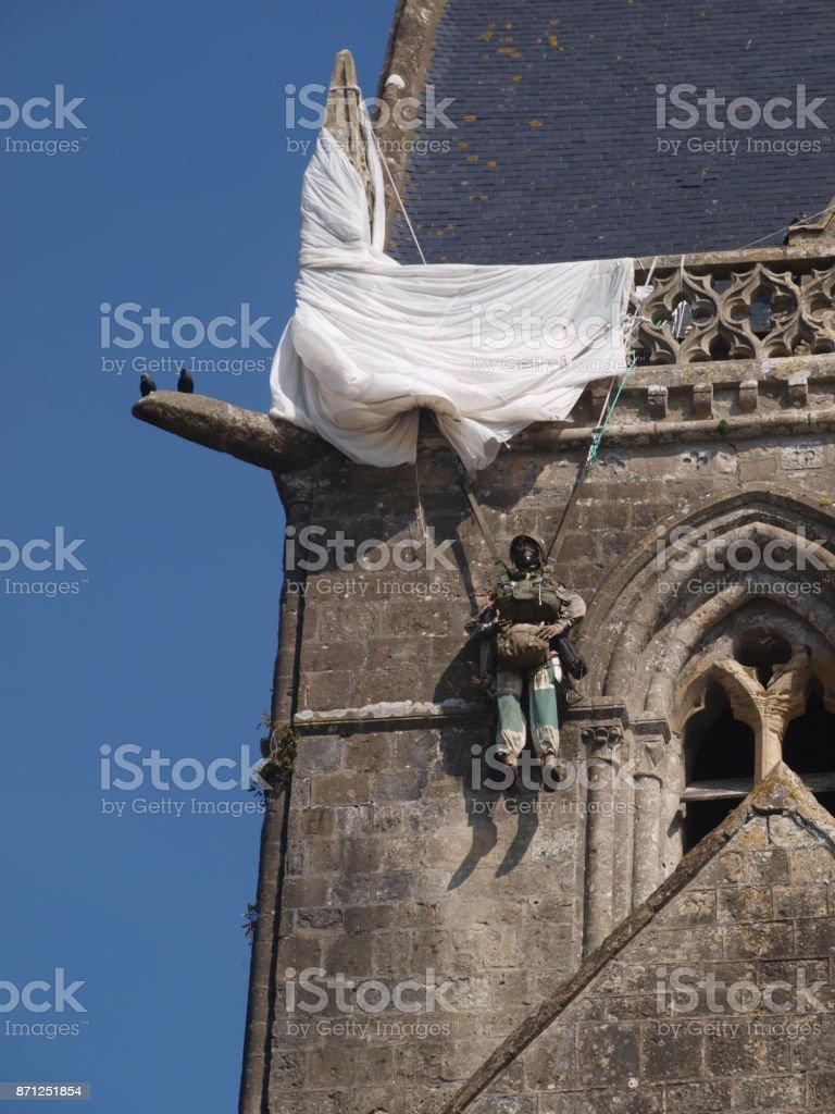kerk in Sainte-Mère-Église, met de pop van een parachutist John Steele met een parachute gevangen op de torenspits van de gemeente kerk tijdens D-day in Normandië, tweede Wereldoorlog 2 foto
