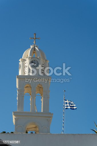 Typical detail of a bell tower of an orthodox white church in the village of megalochori, santorini, cyclades, greece. Greek flag in the blue sky