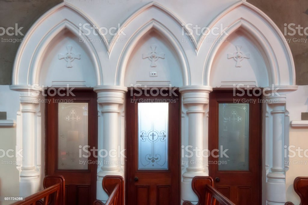 Church interior confessional booths framed by arches and columns. stock photo