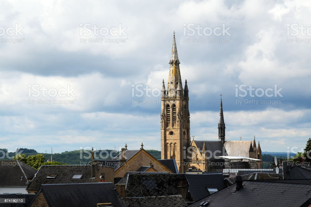 church of arlon over the roofs of the old town against a cloudy sky with copy space, belgium, europe stock photo
