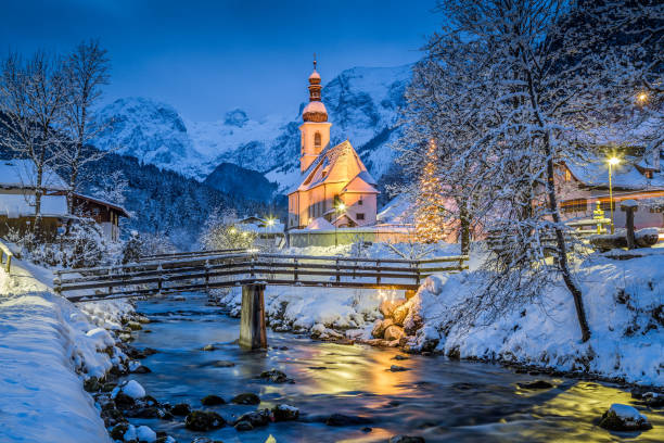 Church of Ramsau in winter twilight, Bavaria, Germany Beautiful twilight view of Sankt Sebastian pilgrimage church with decorated Christmas tree illuminated during blue hour at dusk in winter, Ramsau, Nationalpark Berchtesgadener Land, Bavaria, Germany village stock pictures, royalty-free photos & images