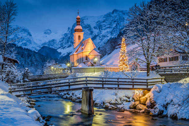 Church of Ramsau in winter twilight, Bavaria, Germany Beautiful twilight view of Sankt Sebastian pilgrimage church with decorated Christmas tree illuminated during blue hour at dusk in winter, Ramsau, Nationalpark Berchtesgadener Land, Bavaria, Germany bavarian alps stock pictures, royalty-free photos & images