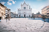 low angled view on Piazza Santa Croce Square with the main Front of Santa Croce Church.  Ghostly tourists figures wandering around