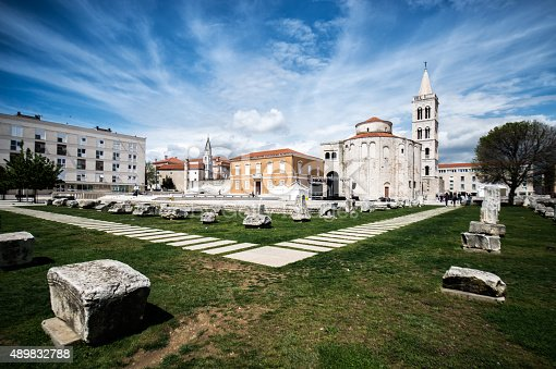 Monumental park with Church of St Donat in Zadar, Croatia. Old stones are placed on the grass area. Cathedral and other buildings are in the background.