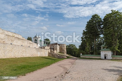 Church of St. Sergius of Radonezh and old Izborsk fortress, Nikolsky's defense sleeve, gates and St. Nicholas Cathedral of 14th century behind the fortified walls. Pskov region, Russia.