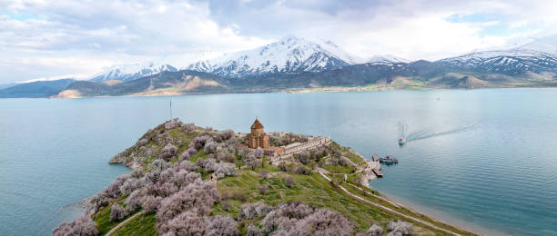 Church of the Holy Cross is Armenian cathedral on  Akdamar Island  in Van city, Eastern Anatolia in Turkey. Panorama ( panoramic ) view. Amazing spring view of Armenian Church of the Holy Cross on Akdamar Island (Akdamar Adasi), Lake Van/Turkey. Surrounded by tree in blossom, in a middle of Akdamar Island. armenian culture stock pictures, royalty-free photos & images