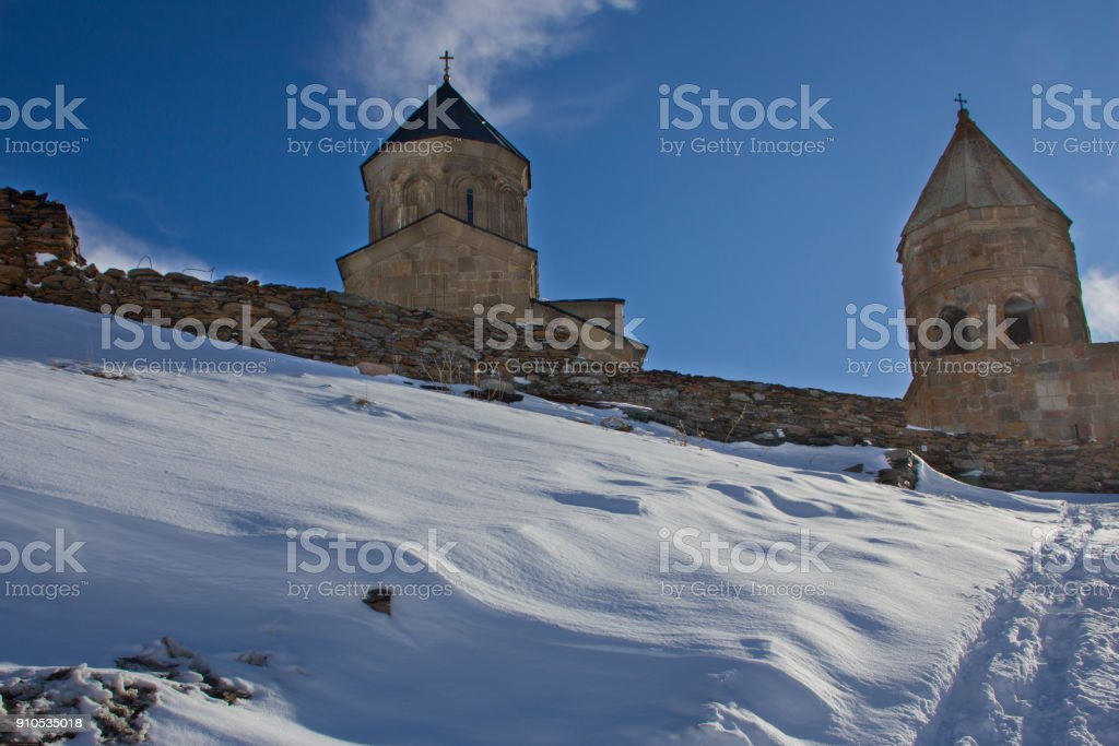 Church of the Holy Trinity in Gergeti, Georgia. The church is in the midst of the snow-capped mountain peaks, a winter snowy morning. stock photo