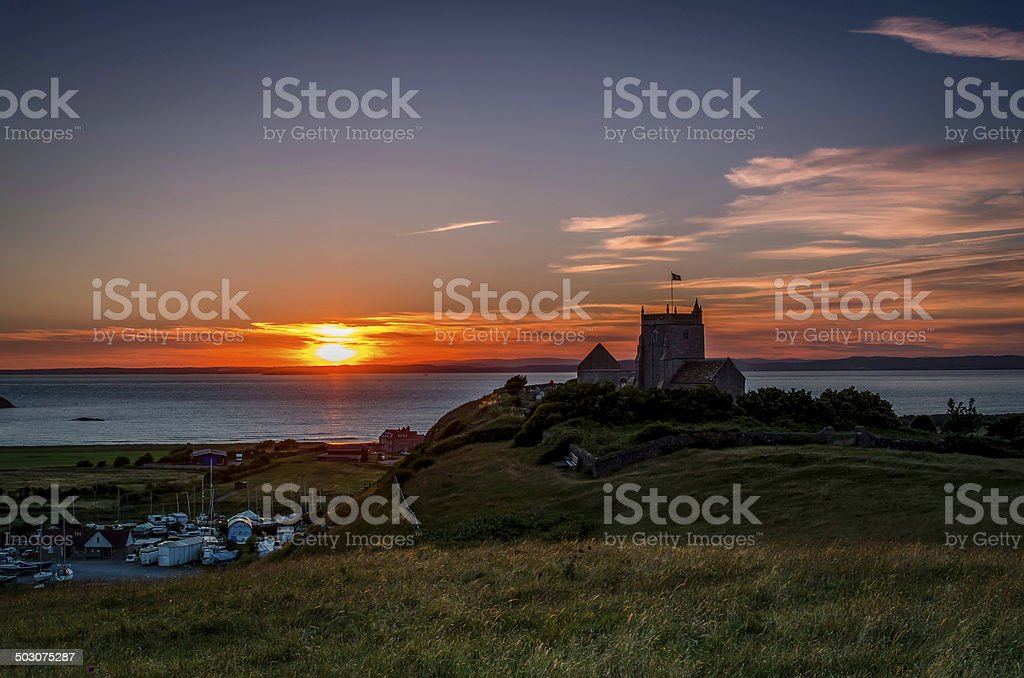 church on a hill with sun setting in background, stock photo