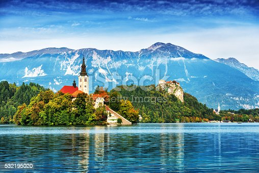 Lake Bled located in Slovenia Europe. There is a Church on the Island and ancient castle on top of a rock. Beautiful blue sky with dramatic cloudscape over the reflection in the Bled Lake. Story in such a beautiful sunny day on sunset. European Alps in the background.
