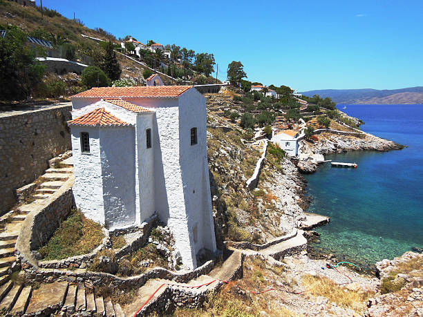 Church on rocks at Hydra Island Ancient stone church by Hydra, on the rocks at the edge of emarald green and blue waters', restored and painted white rymdraket stock pictures, royalty-free photos & images
