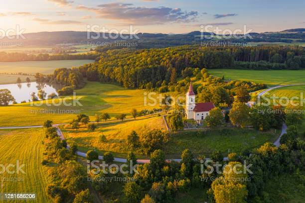 Photo of Church on the hill with sunlit summer landscape from above. Aerial view of Bysicky