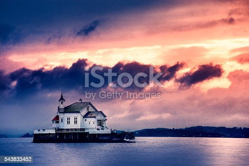 Old Church Perched on Stone in The Middle of Norwegian Fjord at sunset storm.