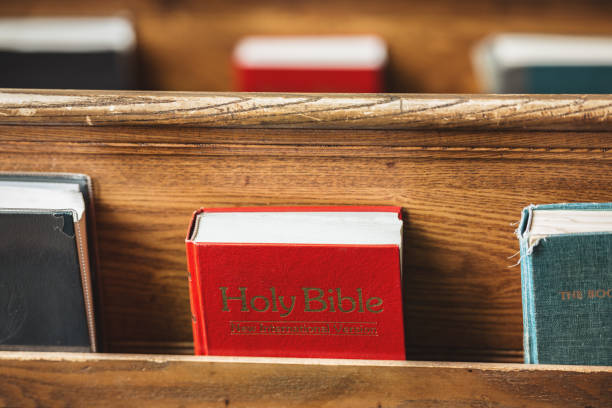Church pew bibles A detail of bibles and hymn books in an old church. pew stock pictures, royalty-free photos & images