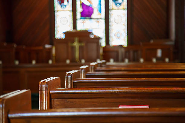 church pews with stained glass beyond pulpit - church stock photos and pictures