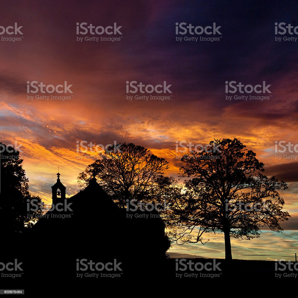 Church silhouetted against a sunset stock photo