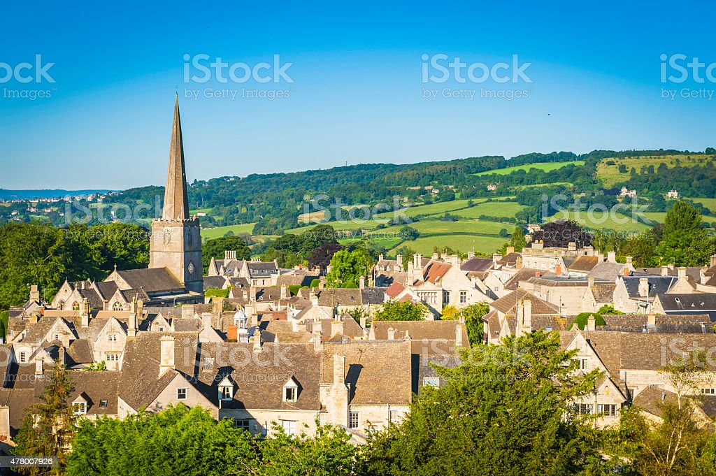 Church spire over pretty Cotswold village cottages green summer fields stock photo