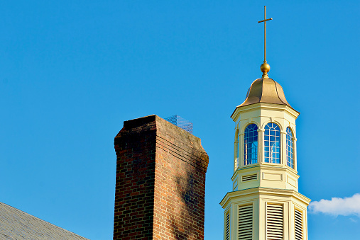 The steeple of a historic church stands out against a blue sky on a hot, summer day.