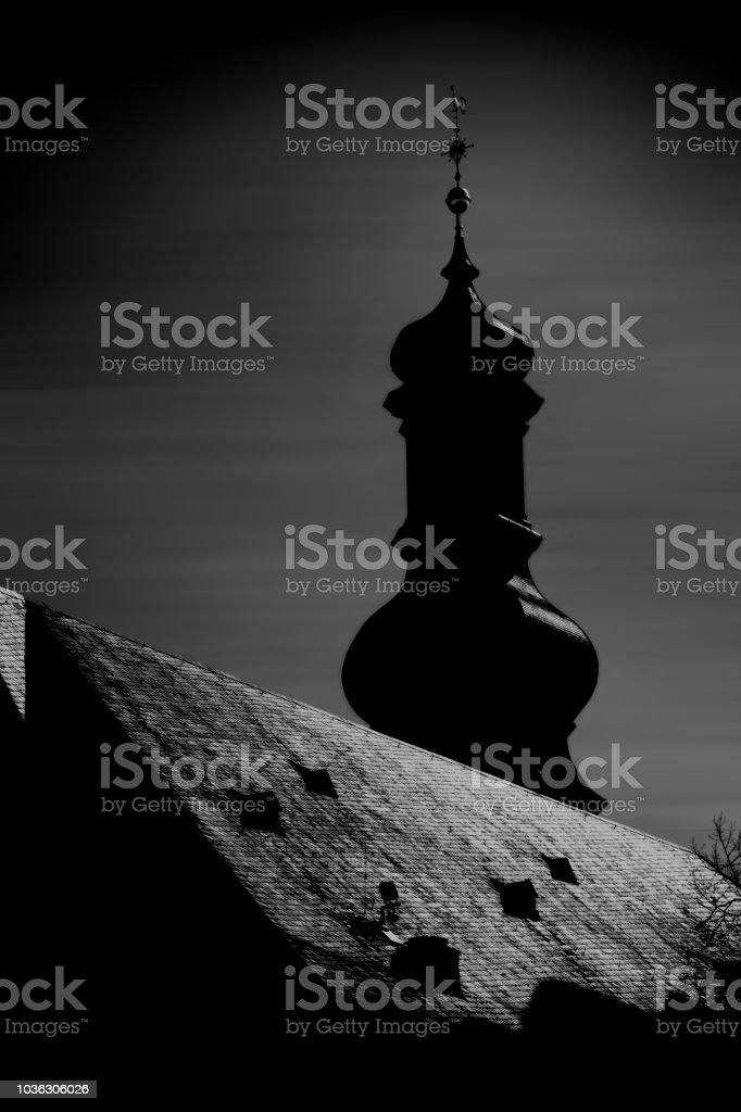 The silhouette of a church tower in the incoming moonlight against a...