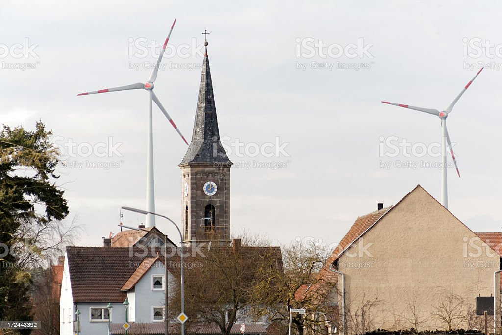 church tower with windturbines stock photo