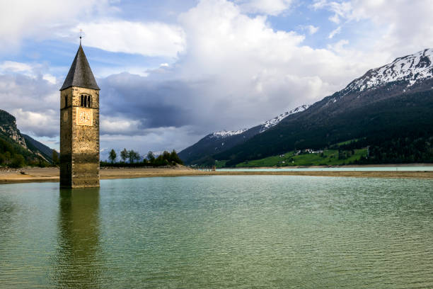 Church under water, drowned village, mountains landscape and peaks in background. Reschensee Lake Reschen Lago di Resia. Italy, Europe, Südtirol, South Tyrol, Upper Adige, Alto Adige stock photo