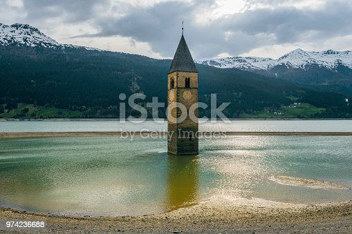 istock Church under water, drowned village, mountains landscape and peaks in background. Reschensee Lake Reschen Lago di Resia. Italy, Europe, Südtirol, South Tyrol, Upper Adige, Alto Adige 974236688