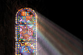 Blues and Yellows in a stained glass window inside of a chapel.