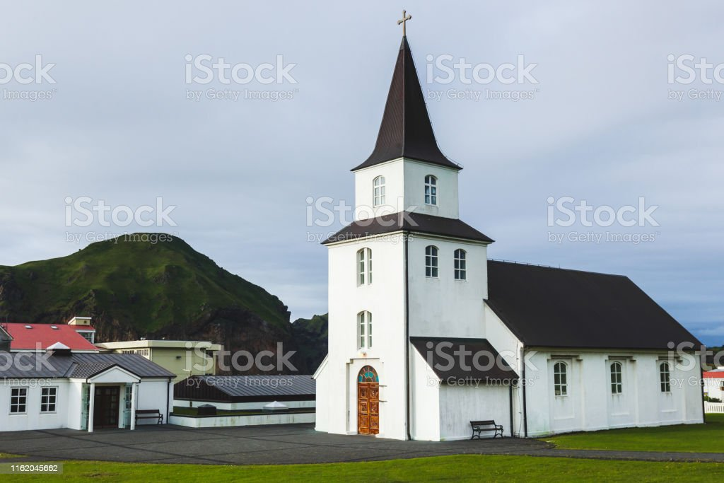 Kirche mit schwarzem Dach und weißen Wänden im traditionellen nordischen minimalistischen Stil auf der Insel Vestmannaeyjar Heimaey in Island. Einfache Architektur, grünes Gras, niemand um. - Lizenzfrei Alt Stock-Foto