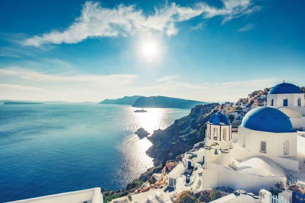 kyrkor i oia, santorini island i grekland, på en solig dag med dramatisk himmel - santorini bildbanksfoton och bilder