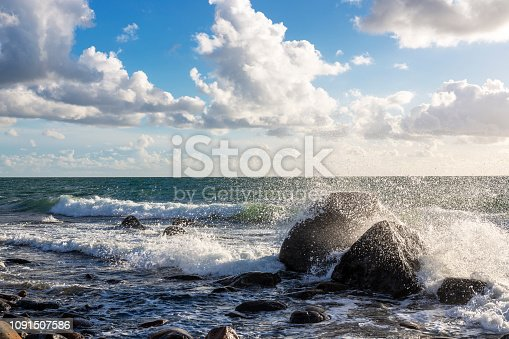 Storm by the sea throws water on stones