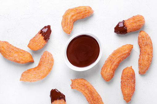 Churros and chocolate sauce on the white table. Spanish dessert. Top view