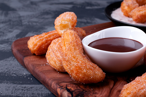 Churros and chocolate sauce on the wooden board. Spanish dessert